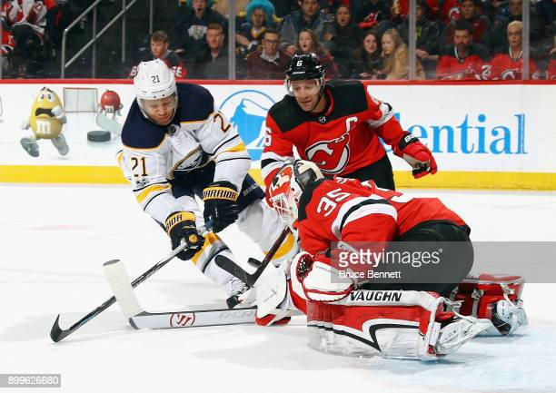Cory Schneider of the New Jersey Devils makes the first period save on Kyle Okposo of the Buffalo Sabres at the Prudential Center on December 29 2017...