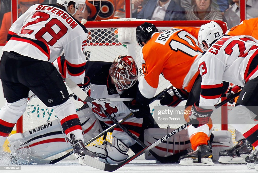 Cory Schneider #35 of the New Jersey Devils makes the kick save as Brayden Schenn #10 of the Philadelphia Flyers looks for the rebound during the third period at the Wells Fargo Center on October 9, 2014 in Philadelphia, Pennsylvania. The Devils defeated the Flyers 6-4.