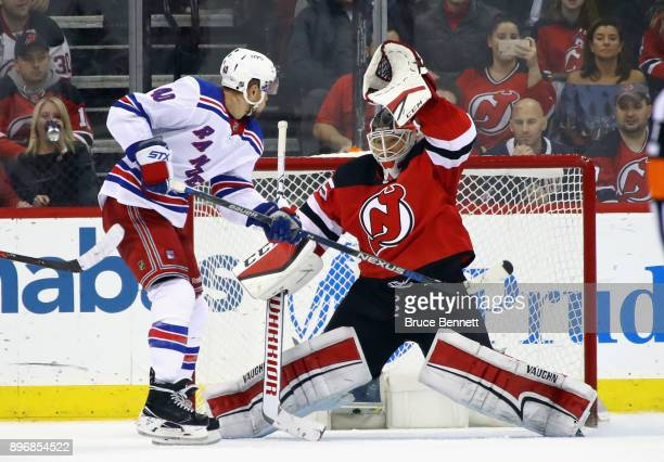 Cory Schneider of the New Jersey Devils makes the save on Michael Grabner of the New York Rangers in overtime at the Prudential Center on December 21...