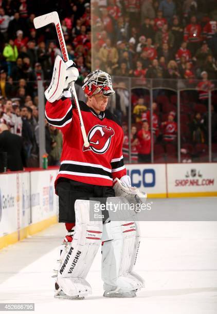 Cory Schneider of the New Jersey Devils salutes the fans after the game against the Buffalo Sabres at Prudential Center on November 30 2013 in Newark...