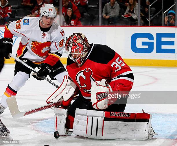 Cory Schneider of the New Jersey Devils stops a shot as Sam Bennett of the Calgary Flames waits for the rebound in the first period on January 192016...