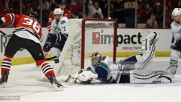Cory Schneider of the Vancouver Canucks dives to make a save against Dave Bolland of the Chicago Blackhawks in Game Six of the Western Conference...