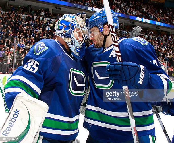 Cory Schneider of the Vancouver Canucks is congratulated by teammate Ryan Kesler after their 6-1 win over the Edmonton Oilers at Rogers Arena on...