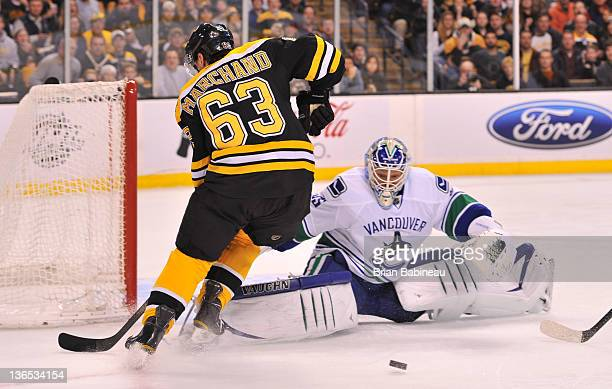 Cory Schneider of the Vancouver Canucks watches the loose the puck against Brad Marchand of the Boston Bruins at the TD Garden on January 7 2012 in...