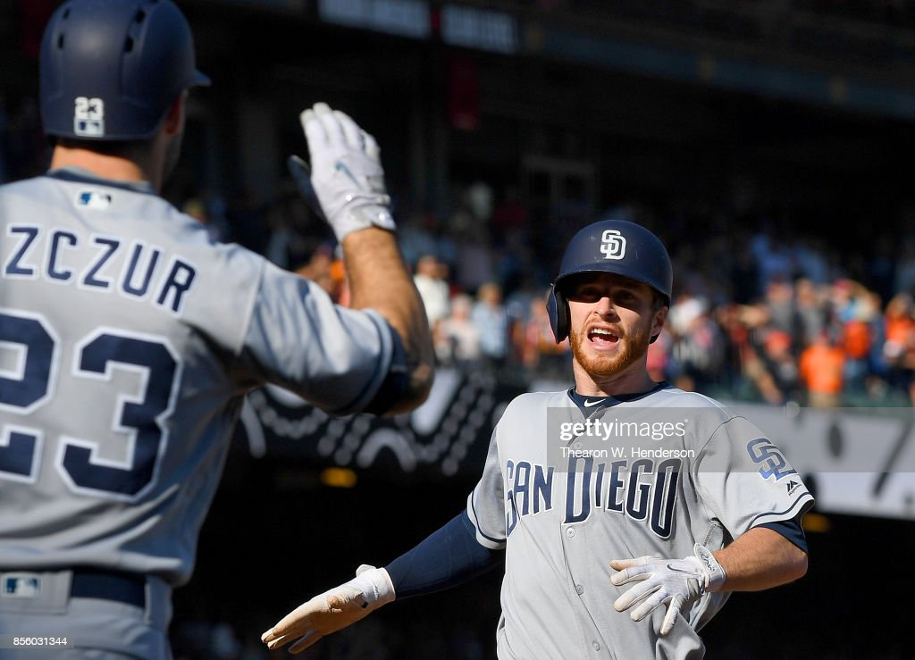 Cory Spangenberg #15 of the San Diego Padres is greeted by Matt Szczur #23 after Spangenberg scored right behind Szczur on a two-run rbi double from Austin Hedges #18 against the San Francisco Giants in the top of the ninth inning at AT&T Park on September 30, 2017 in San Francisco, California. The Padres won the game 3-2.