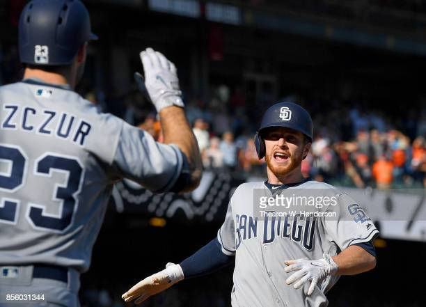 Cory Spangenberg of the San Diego Padres is greeted by Matt Szczur after Spangenberg scored right behind Szczur on a tworun rbi double from Austin...