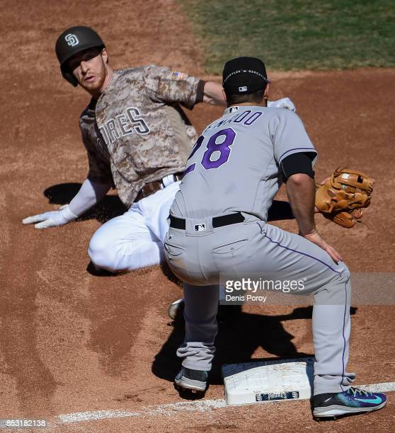 Cory Spangenberg of the San Diego Padres is tagged out by Nolan Arenado of the Colorado Rockies as he tries to steal third bas during the second...