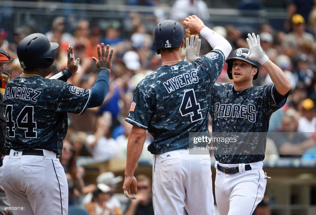 Cory Spangenberg #15 of the San Diego Padres, right, is congratulated by Hector Sanchez #44 and Wil Myers #4 after hitting a three-run home run during the third inning of a baseball game against the San Francisco Giants at PETCO Park on July 16, 2017 in San Diego, California.
