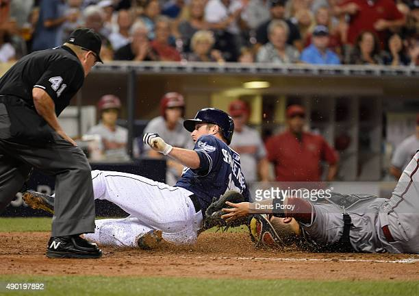 Cory Spangenberg of the San Diego Padres scores ahead of the tag of Welington Castillo of the Arizona Diamondbacks during the sixth inning of a...