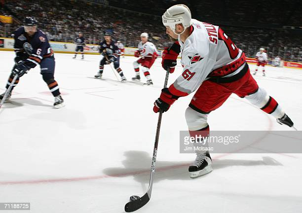Cory Stillman of the Carolina Hurricanes passed the puck against Jaroslav Spacek of the Edmonton Oilers during game four of the 2006 NHL Stanley Cup...