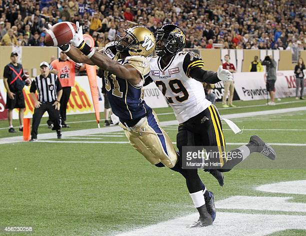 Cory Watson of the Winnipeg Blue Bombers can't keep hold of the ball during an attempted two-point conversion as he gets pressure by Ed Gainey of the...