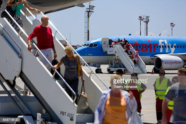 Cos Dodecanese Greece June 13 2015 Passengers are going down an Airbus A320 while some others go in a Boeing B767300ER from jetairfly in Kos Airport