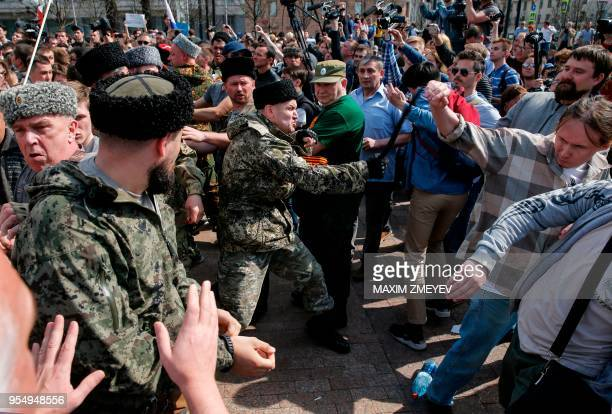 TOPSHOT Cosacks scuffle with opposition supporters during an unauthorized antiPutin rally called by opposition leader Alexei Navalny on May 5 2018 in...