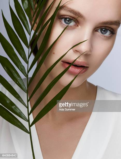 cosmetic beauty shot of a young woman with palm leaf