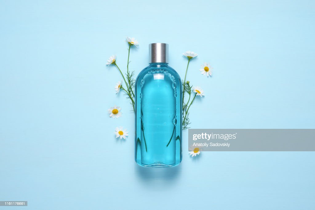Cosmetic bottle and chamomile flowers on blue table top view : Stock Photo