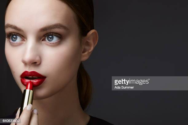 cosmetic portrait of young woman applying lipstick