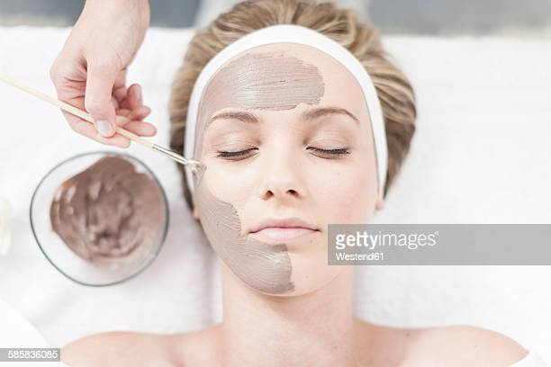 Cosmetician applying beauty mask