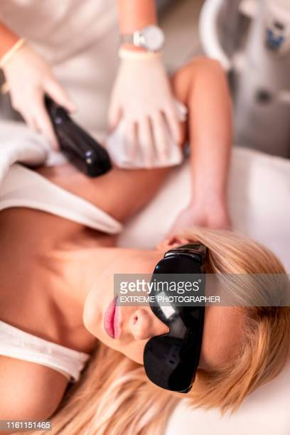 cosmetician performing hair removal procedure from a woman's armpit in a beauty salon - armpit hair woman stock pictures, royalty-free photos & images