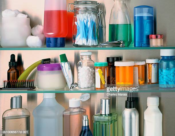 Cosmetics and containers with pills on shelf