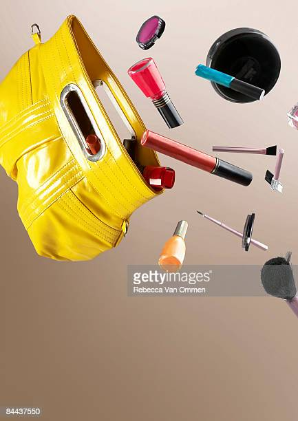 cosmetics falling out of a hand bag
