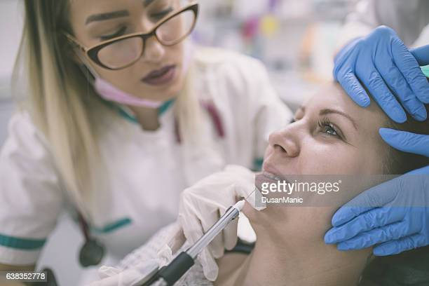 Cosmetologist making botox injection in female lips