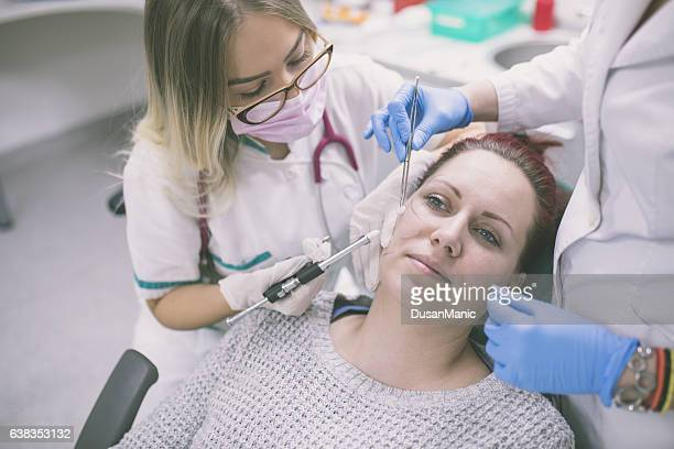 Cosmetologist making botox injection