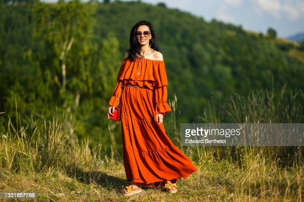Cosmina Pasarin wears sunglasses, an off-shoulder orange ruffled gathered and pleated long dress with flared sleeves, a red bag, platform sandals, on...