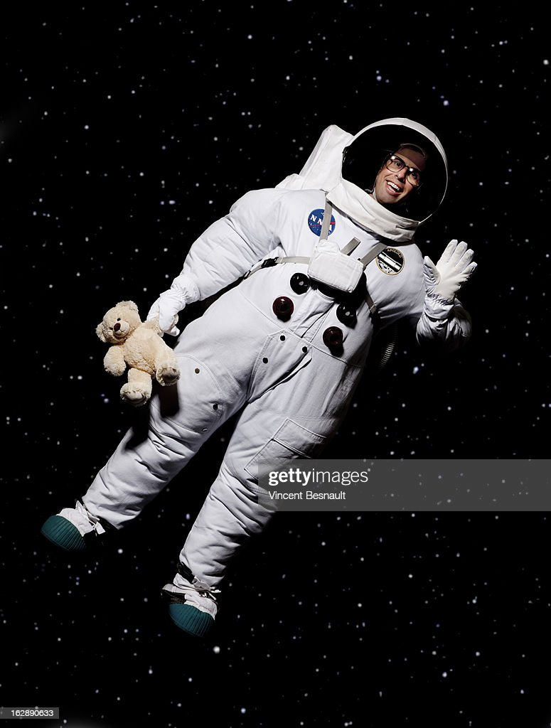 cosmonaut holding a teddy bear in space ストックフォト getty images