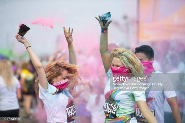 Cosondra Sjostrom left and Kimmi Wahl both of Los Angeles celebrate after finishing the Color Run Hero Tour 5K in Huntington Beach on Saturday...