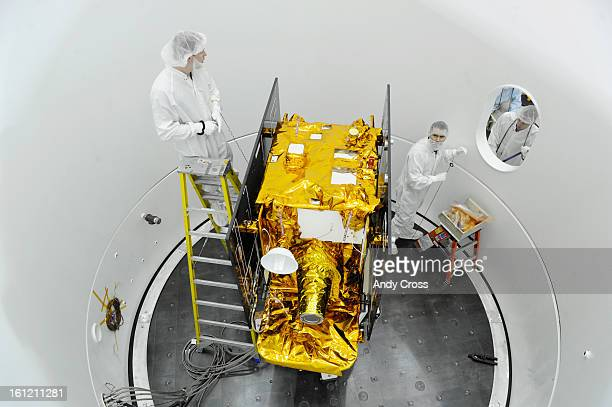 """Spacecraft technicians, Tim Waltman, left, and Manny Nevarez, right, work on the GRAIL B spacecraft inside a """"rough vacuum chamber"""" at Lockheed..."""
