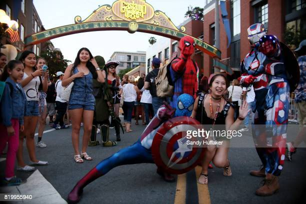 Cosplay characters dressed as Spiderman pose for pictures along 5th Avenue in the Gaslamp Quarter during Comic Con International on July 20 2017 in...