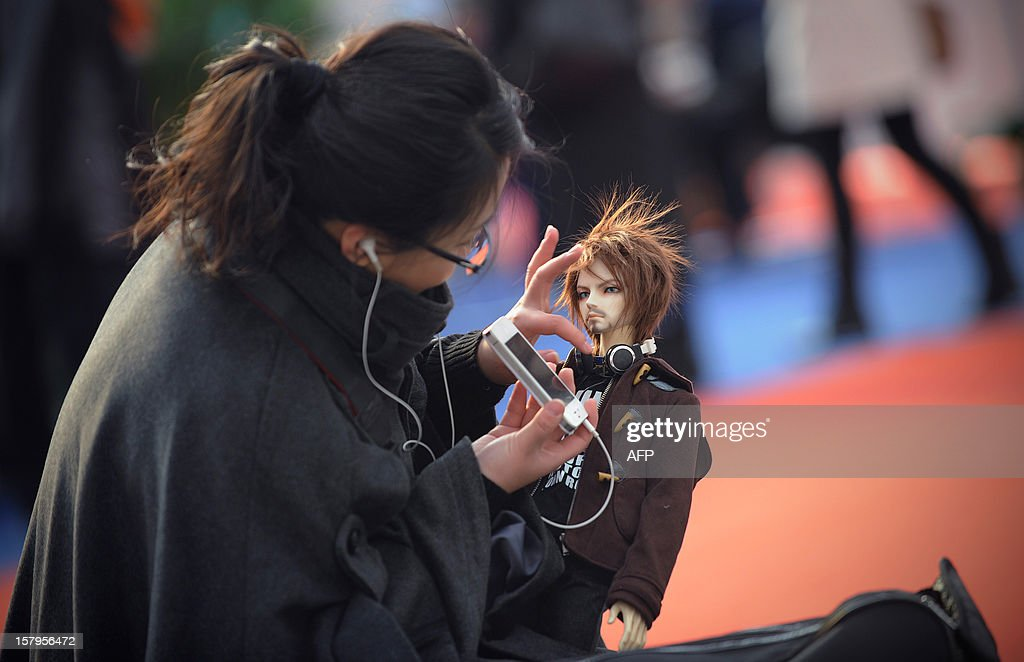 A 'cosplay' fan prepares a dressed up doll for the International Anime Fair in Beijing on December 8, 2012. The fair is being held at the Beijing Crab Island International Convention and Exhibition Centre from December 1 to 9.