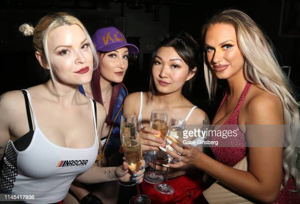 Cosplay models Dangrrr Doll Holly Wolf Gaius Cosplay and Eden Victoria make a champagne toast during Larry Flynt's Hustler Club The Gamer Convention...