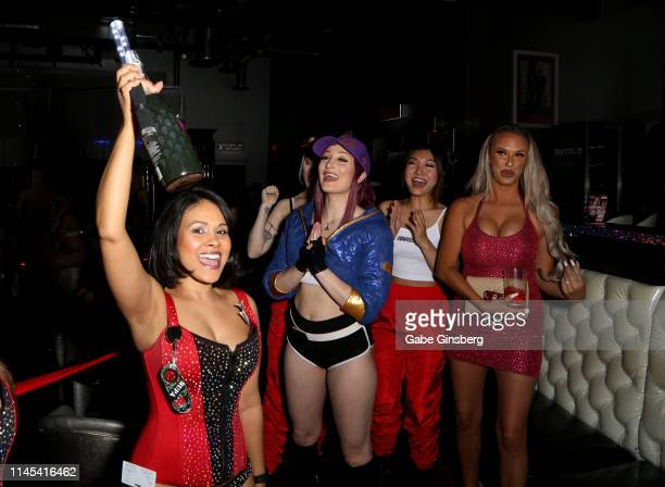 Cosplay models Dangrrr Doll Holly Wolf Gaius Cosplay and Eden Victoria react to a waitress bringing champagne during Larry Flynt's Hustler Club The...