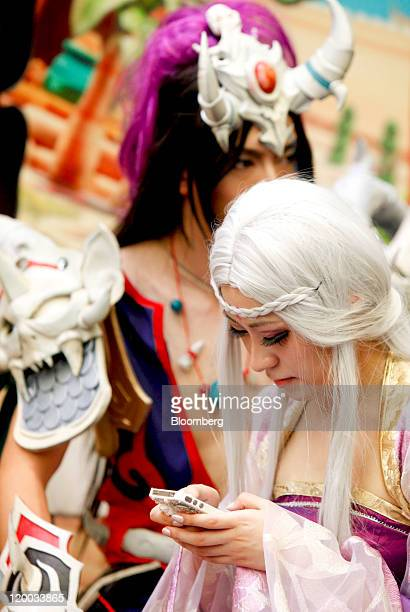 A cosplay performer checks her cell phone at the ChinaJoy Expo also known as the China Digital Entertainment Expo and Conference in Shanghai China on...