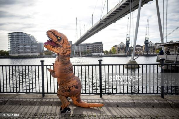 A cosplayer dressed as a dinosaur attends the MCM Comic Con at ExCeL exhibition centre in London on October 28 2017