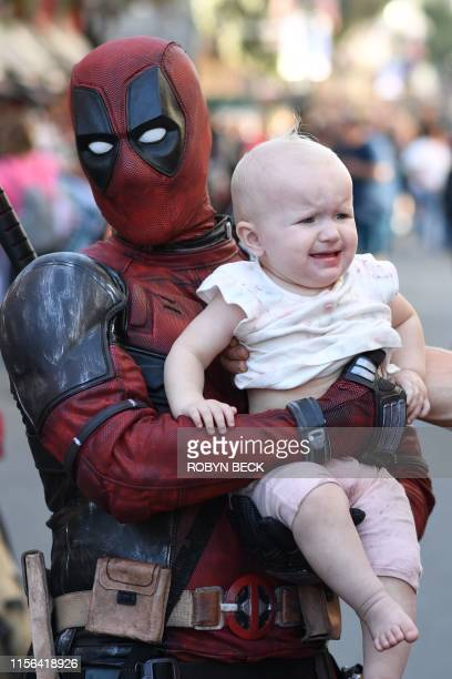 Cosplayer dressed as Deadpool poses for a photo with a baby outside the San Diego Convention Center on the first day of the 2019 Comic-Con...