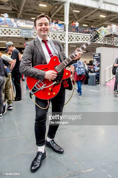 A cosplayer in character as Back to the Future 1 Marty McFly singing Johnny B Goode from the Prm scene in the film seen during London Film and Comic...