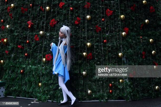 A cosplayer poses for photos during a costume event at a shopping mall in Hanoi on December 21 2019 Cosplay short for costume play is a subculture...