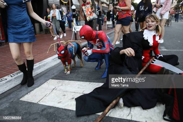 Cosplayers along with a dog dressed as SpiderMan gather outside San Diego ComicCon on July 19 2018 in San Diego California Thousands of revelers are...