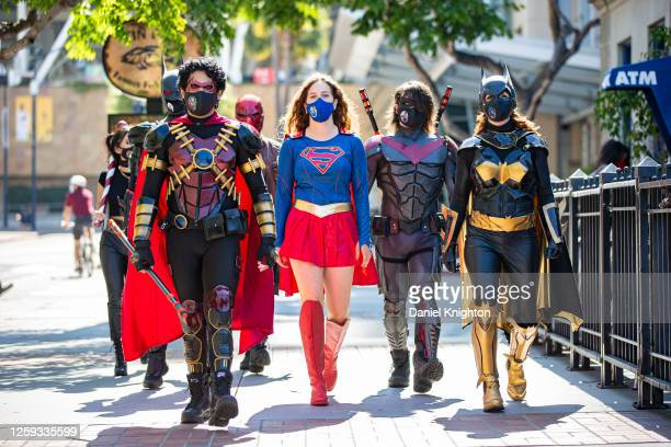 Cosplayers Brandon Buisan as Red Robin, Nona Golan as Supergirl, James Lavelle as Nightwing, and Milan Lavelle as Batgirl visit the Comic-Con Shrine...