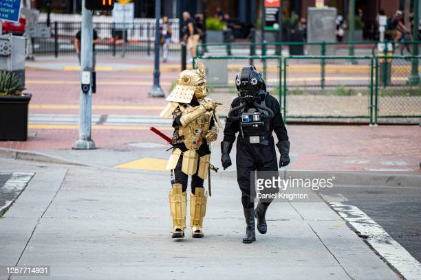 Cosplayers Christopher Canole as Dude Vader and Todd Felton as a TIE Pilot walk towards San Diego Convention Center on July 22, 2020 in San Diego,...