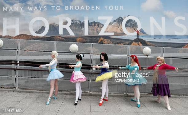 Cosplayers dressed as Disney princesses practice ballet outside the venue as they attend the MCM Comic Con at ExCeL exhibition centre in London on...