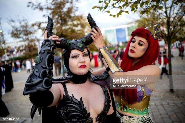 Cosplayers dressed as Maleficent and Ariel from Disney adjust their costumes at the MCM Comic Con at ExCeL exhibition centre in London on October 28...