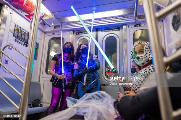 Cosplayers in costumes wield lightsabers on a subway at the 34th Street station on the final day of New York Comic Con at Javits Center on October...