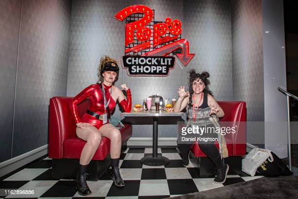 """Cosplayers Leah Thomas as Zoya the Destroya and Erin Thomas as Sheila the She Wolf from the television show """"Glow"""" pose in a display of Pop's..."""