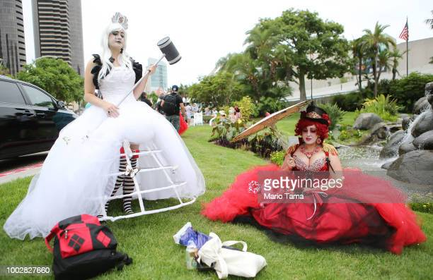 Cosplayers pose while dressed as the White Queen and Queen of Hearts outside ComicCon on July 20 2018 at the San Diego Convention Center in San Diego...
