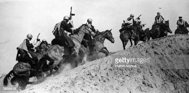 Cossack cavalry equipped with capes steel helmets and submachine guns riding over a height into action