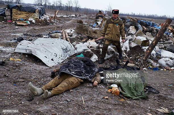 Cossack fighter stands near two dead bodies of Ukrainian soldiers on the outskirt of the town on February 20 2015 in Debltseve Ukraine The strategic...