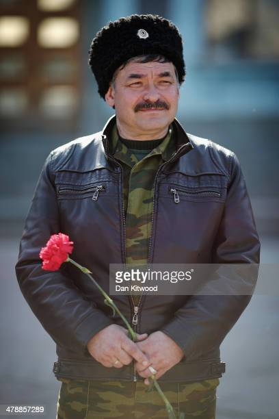 Cossack man holds a flower during a Pro Russian rally in Lenin Square on March 15, 2014 in Simferopol, Ukraine. As the standoff between the Russian...